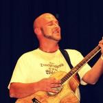 Michael Dietmayr mit Gitarre, singend auf der Bühne